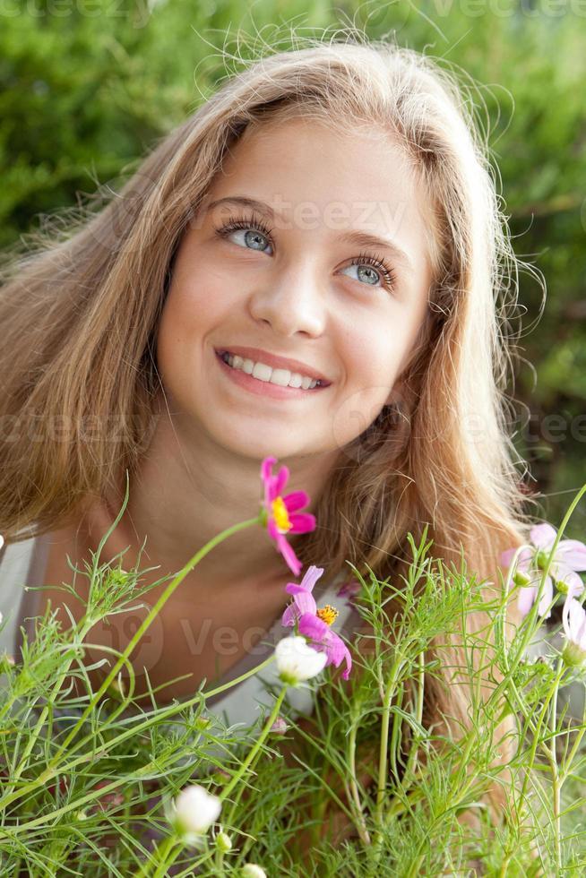 Ritratto di sorridente ragazza bionda sopra i fiori, verde foto