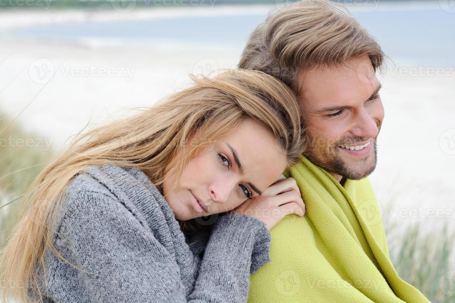 coppia abbracciati in spiaggia, mare autunnale, erba di mare foto