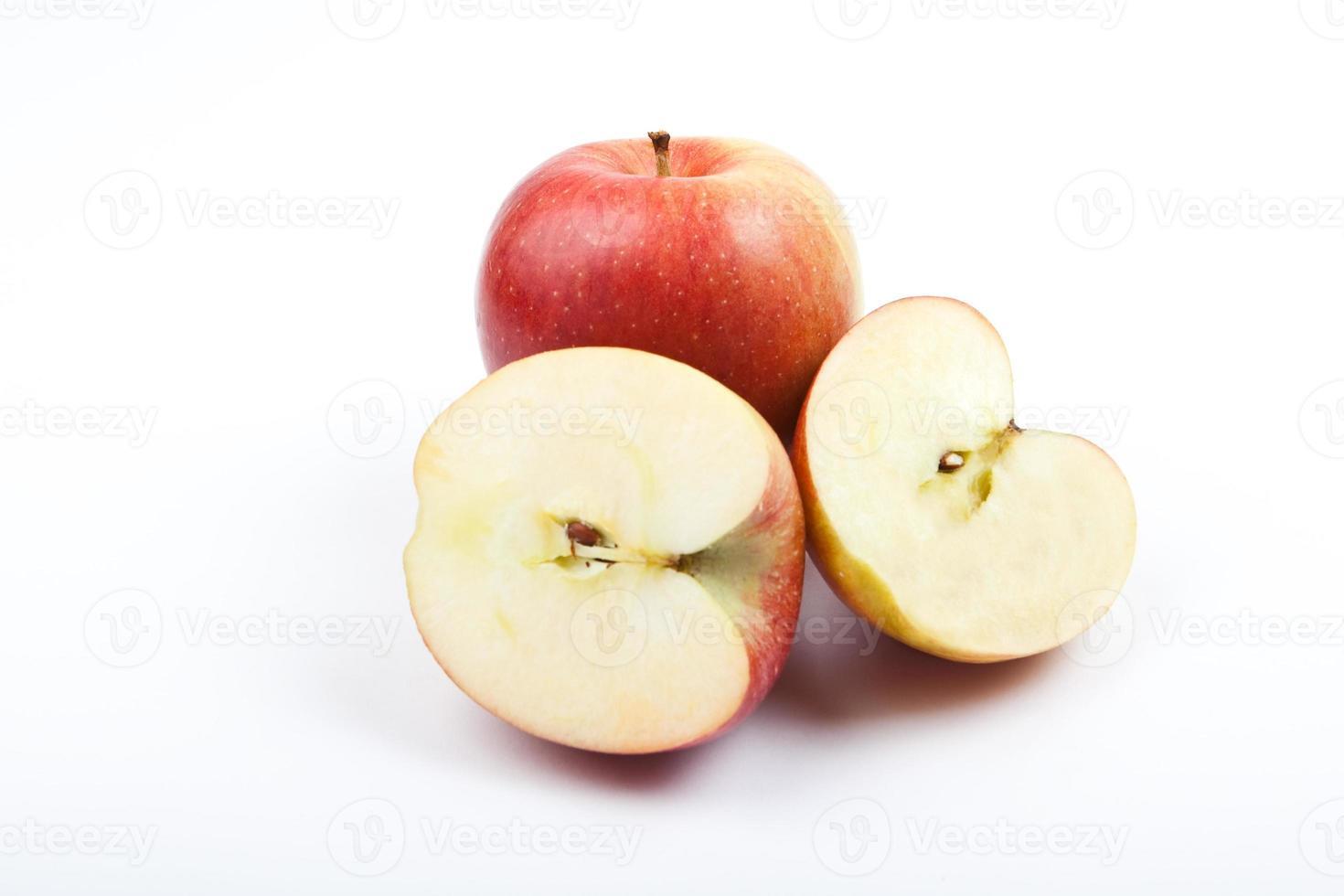 mela rossa e due metà su sfondo bianco foto