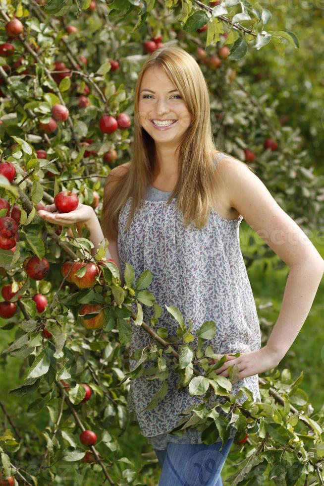 giovane donna di fronte a un albero di mele foto