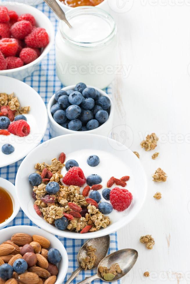 colazione con muesli, yogurt e frutti di bosco su un legno bianco foto