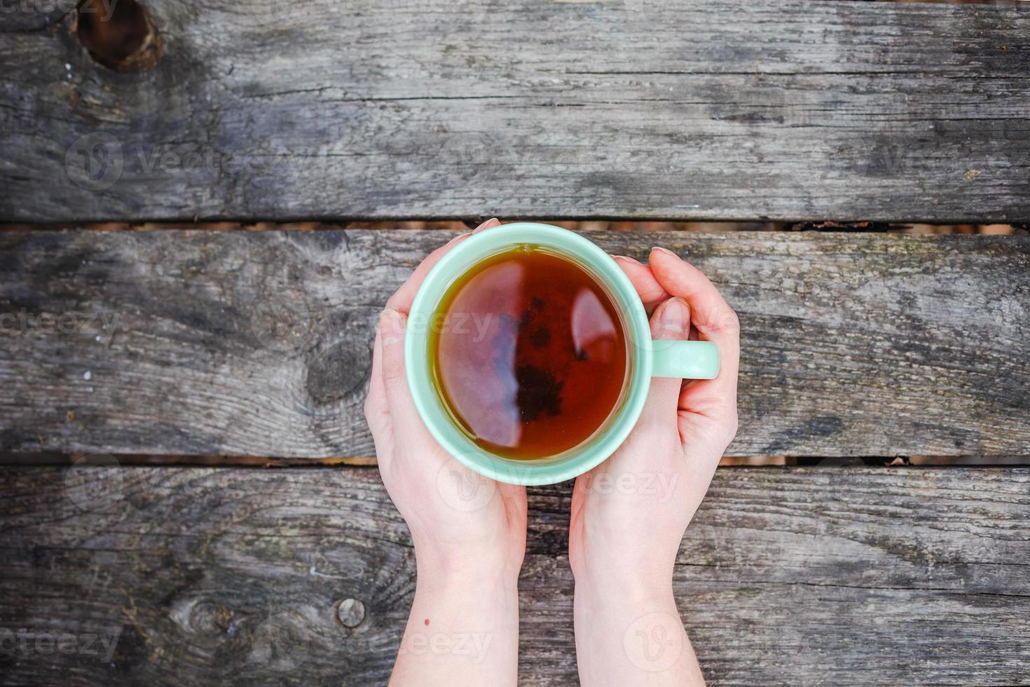 tazza di tè che scalda le mani fredde foto