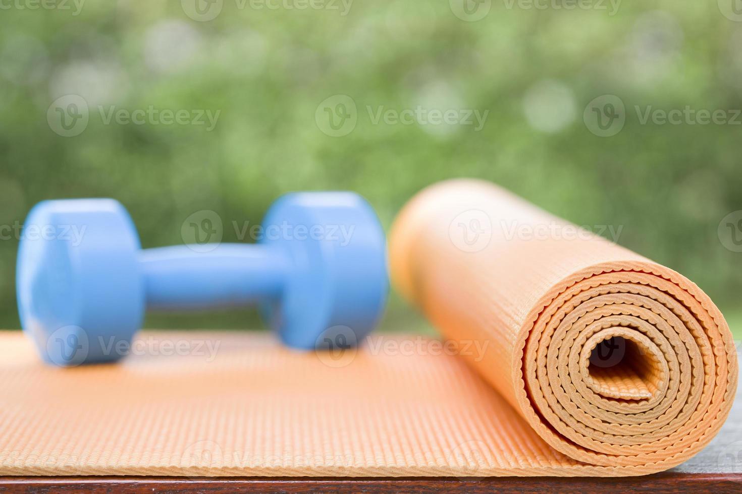 tappetino yoga arancione e manubri blu foto