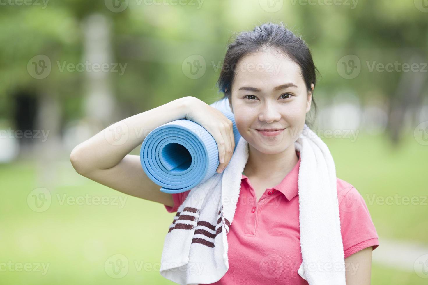 giovane donna che tiene una stuoia di yoga foto