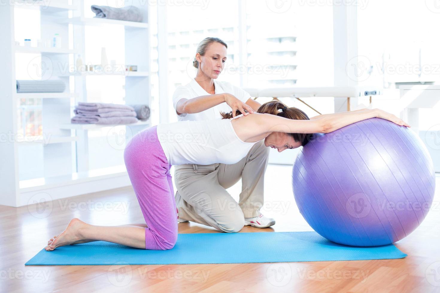 donna d'aiuto dell'istruttore con la palla di esercizio foto