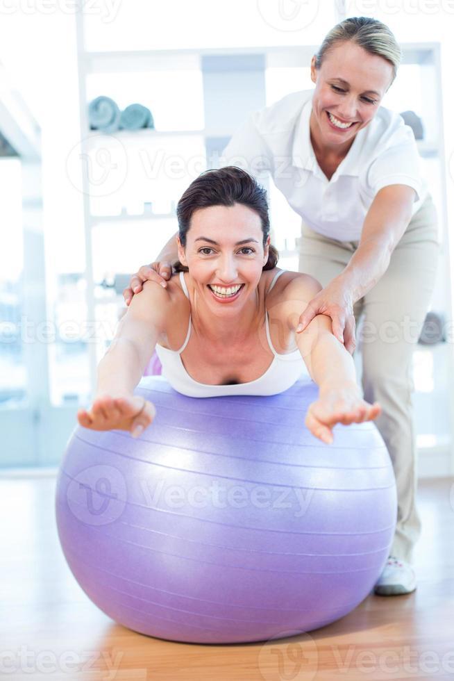 donna d'aiuto dell'istruttore sulla palla di esercizio foto