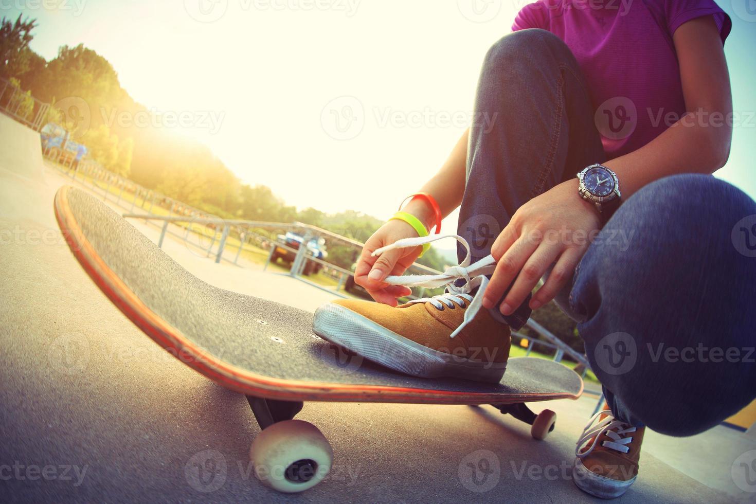 giovane skateboarder asiatico legare i lacci delle scarpe su skateboard foto