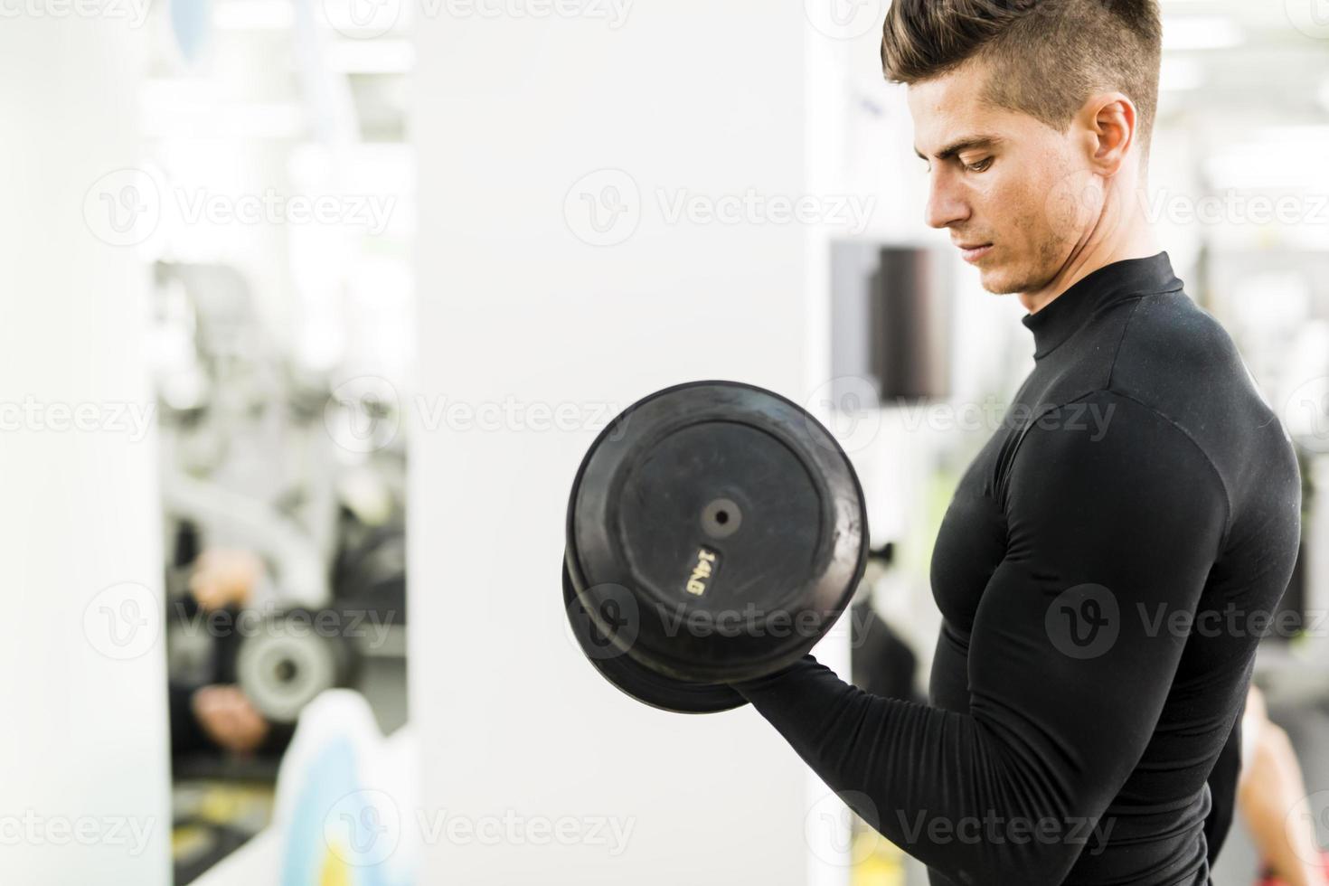 giovane uomo bello allenandovi in palestra foto