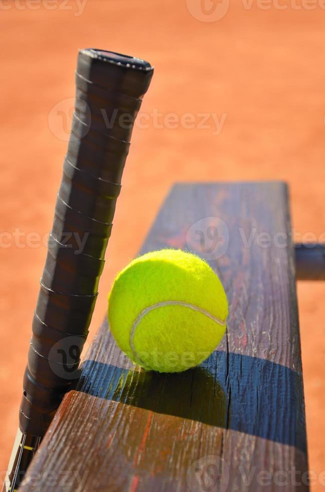 racchetta da tennis e palla in panchina foto