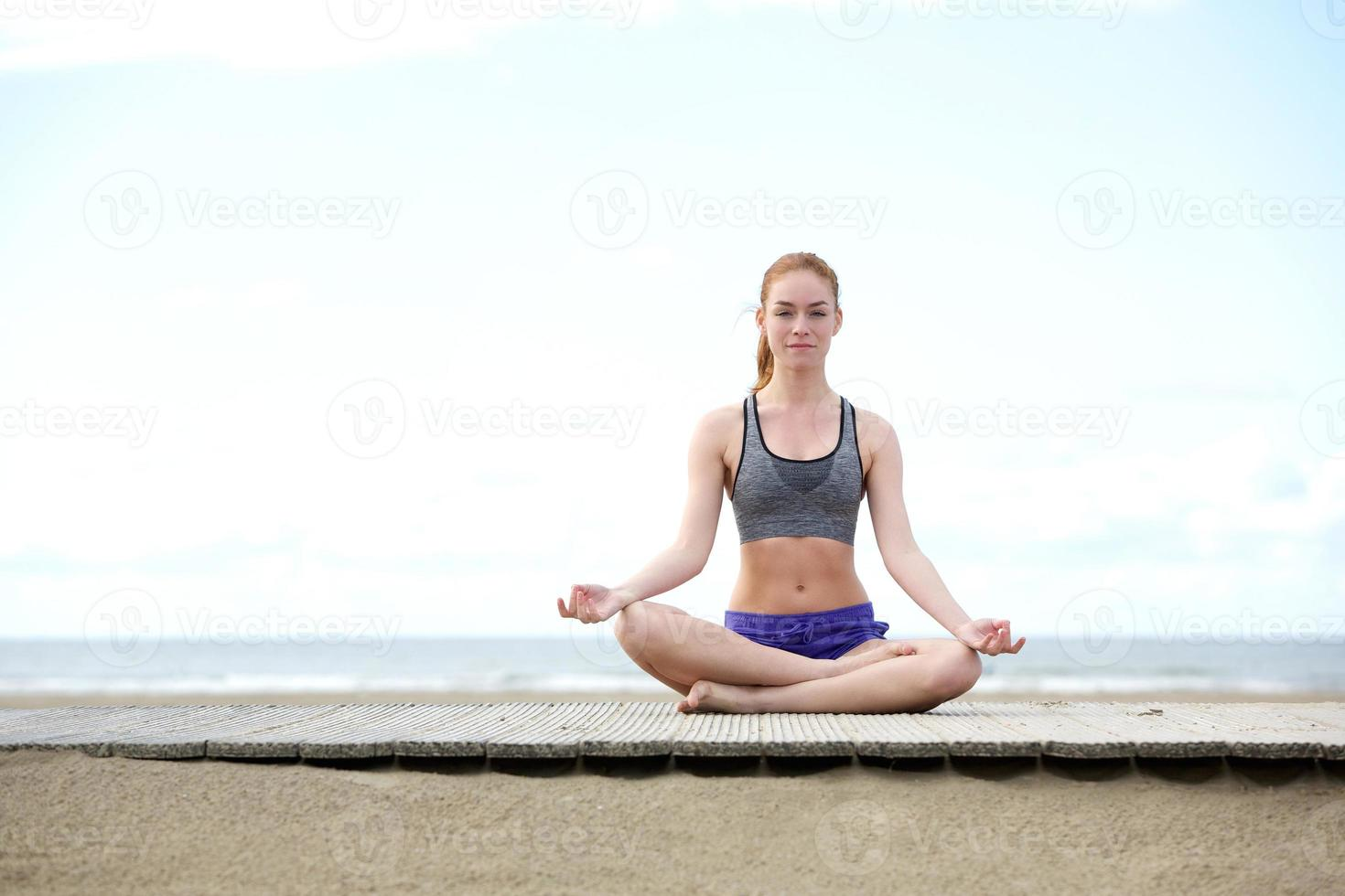 bella giovane donna che si siede all'aperto nella posa di yoga foto