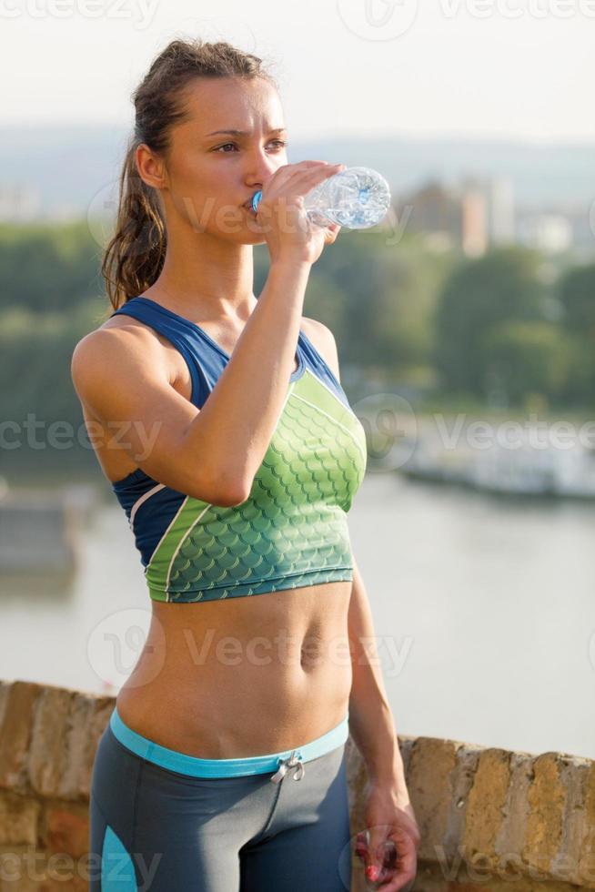 acqua potabile della donna sportiva all'aperto il giorno soleggiato foto