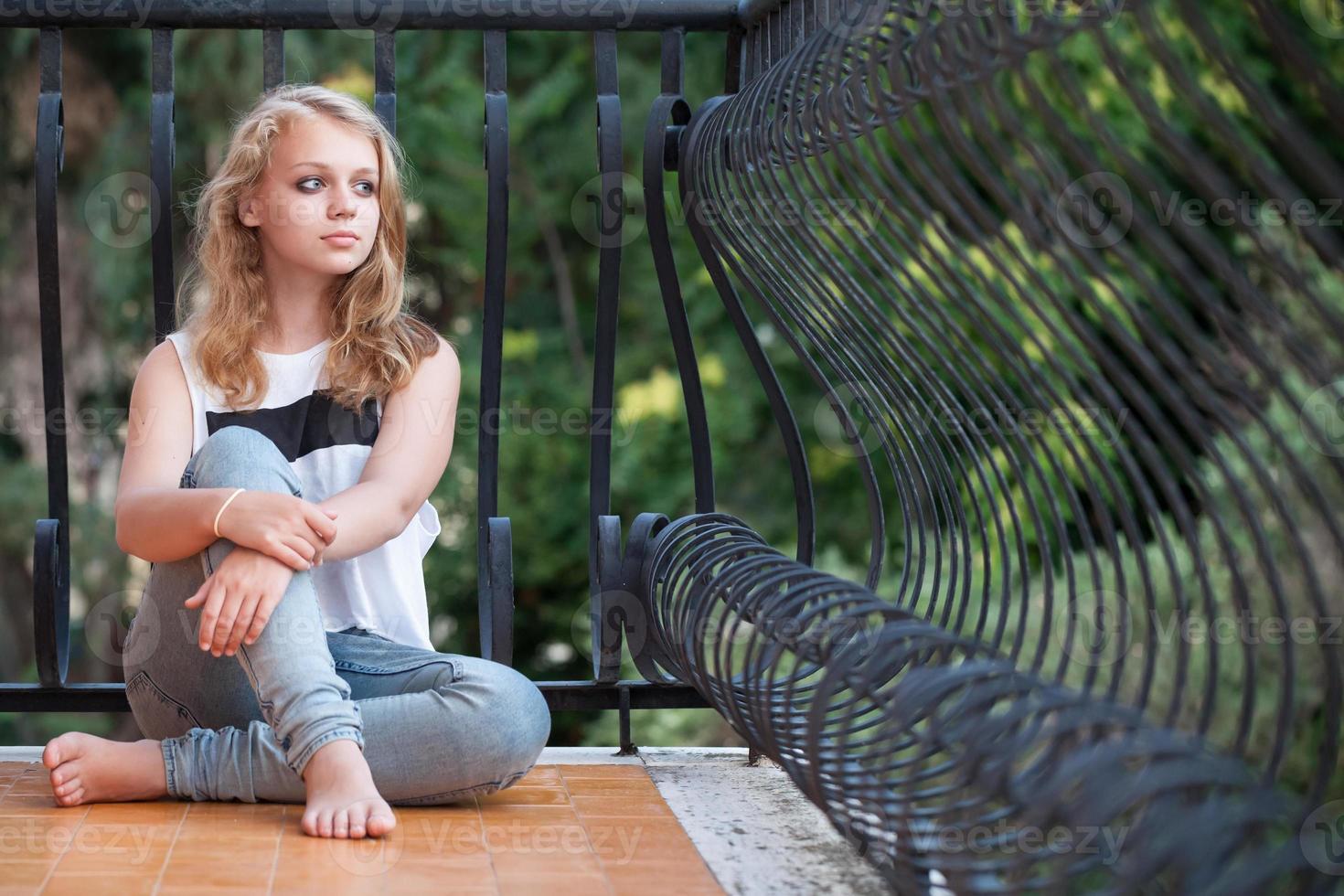 bella ragazza bionda caucasica si siede sul balcone foto
