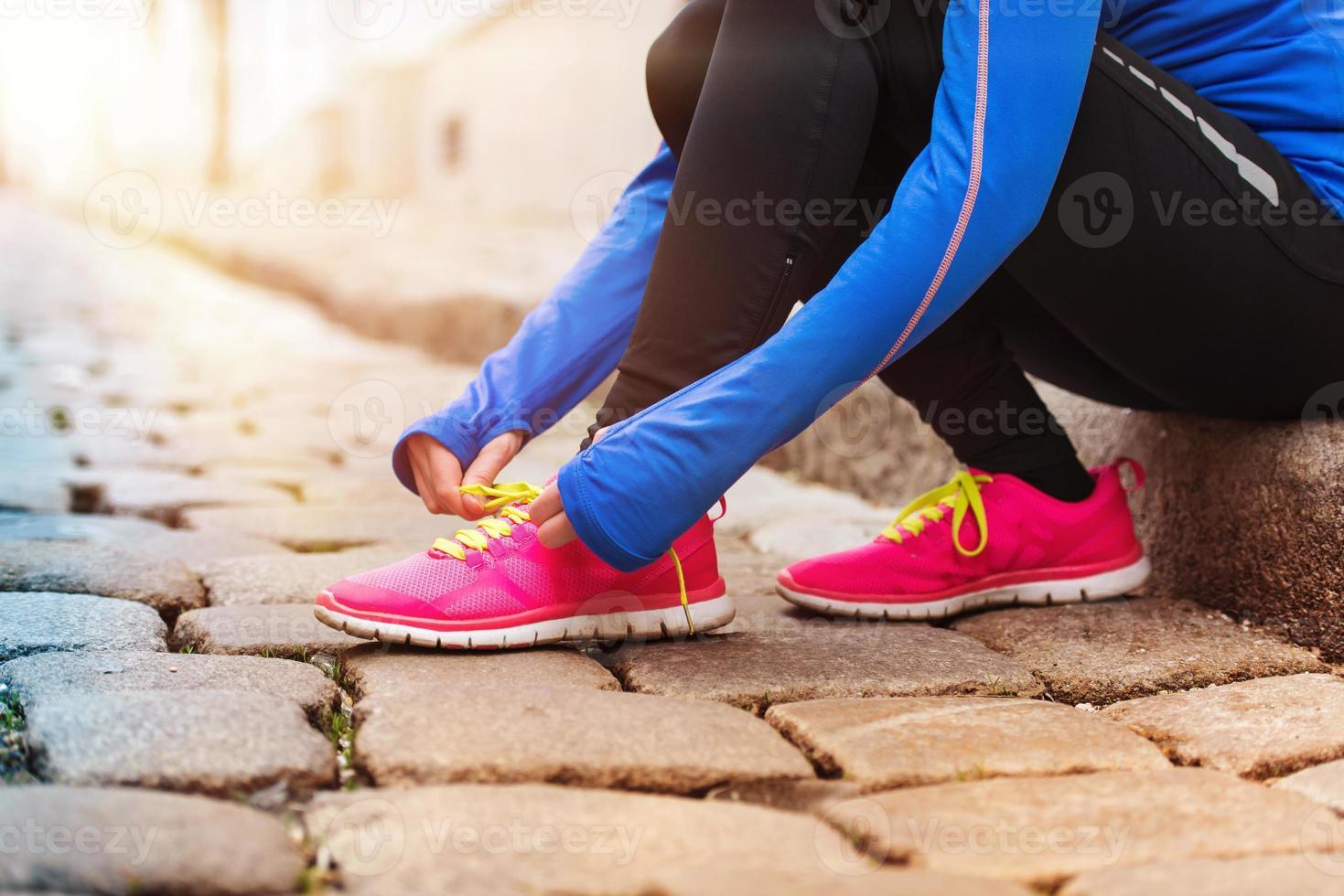 giovane donna che lega le sue scarpe da ginnastica rosa per prepararsi a una corsa foto