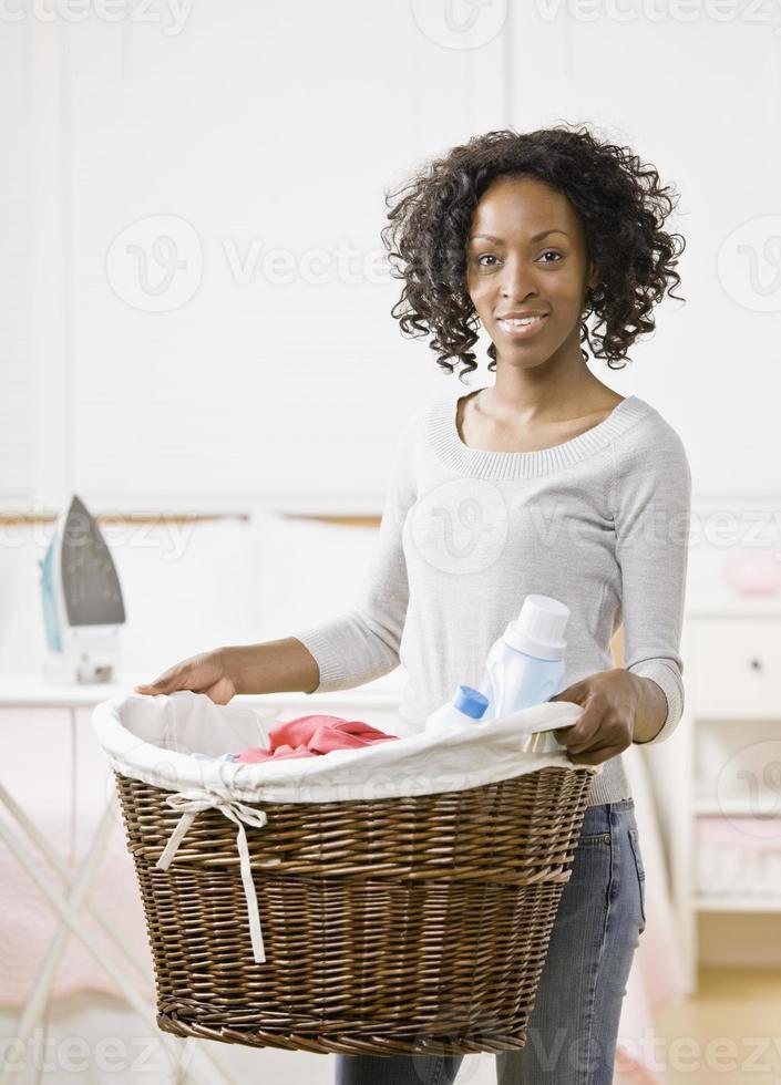 casalinga che trasporta il cesto della biancheria pieno di vestiti foto