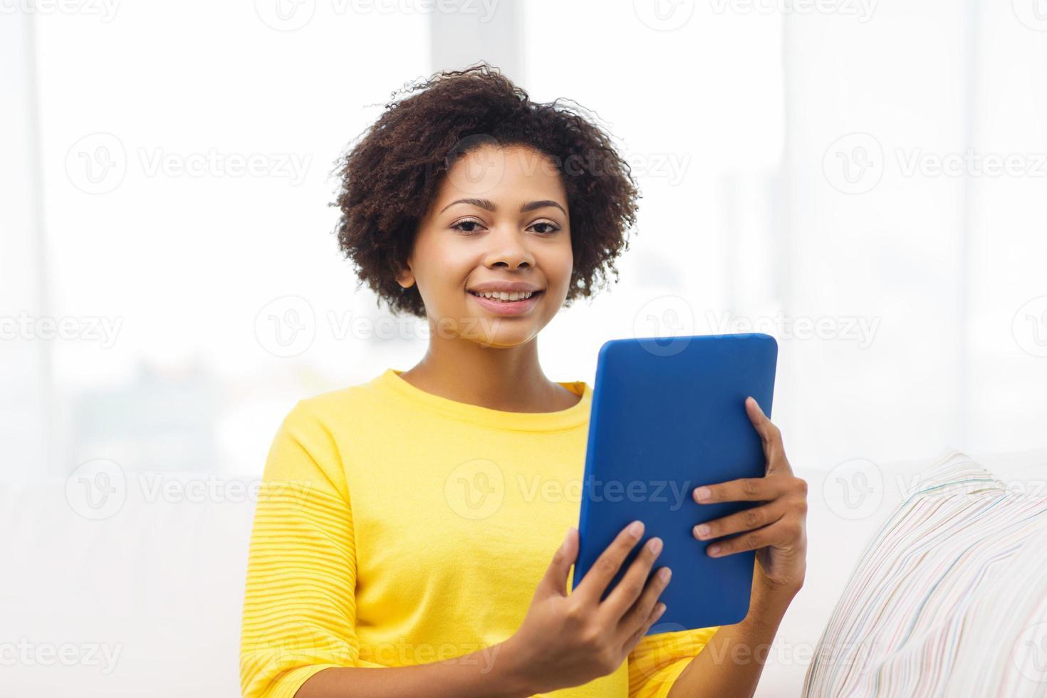 felice donna afro-americana con tablet pc foto