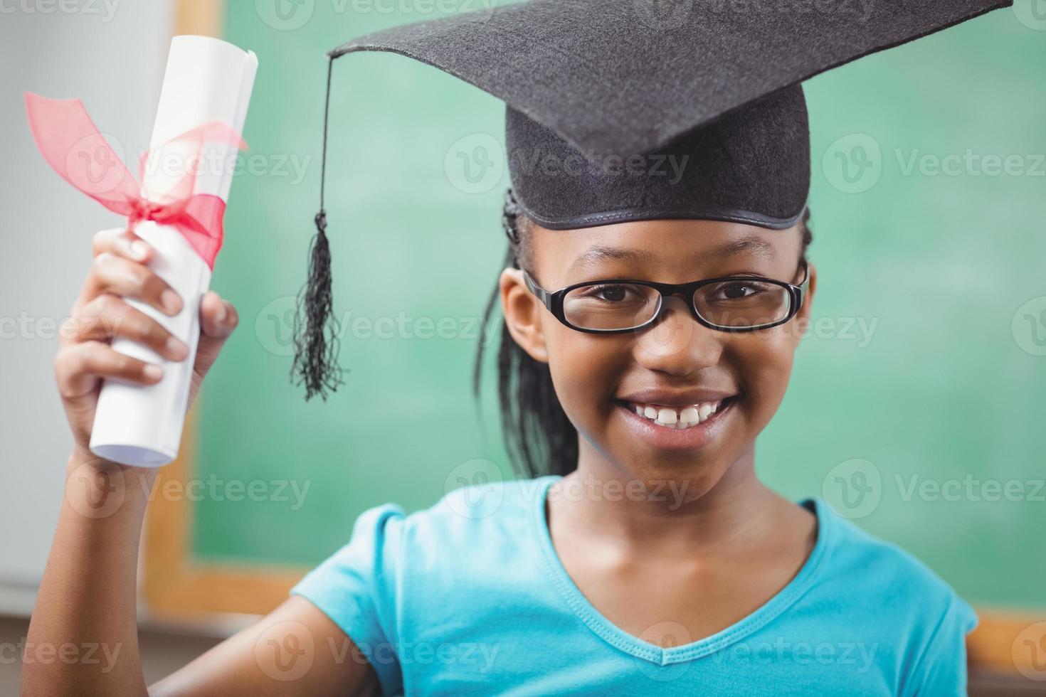 allievo sorridente con bordo di mortaio e diploma foto