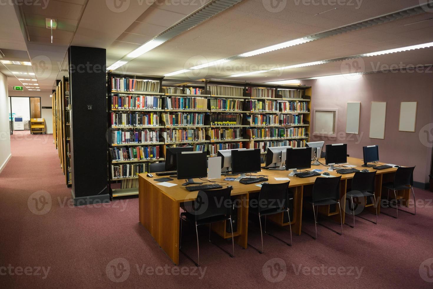banchi di computer in biblioteca foto
