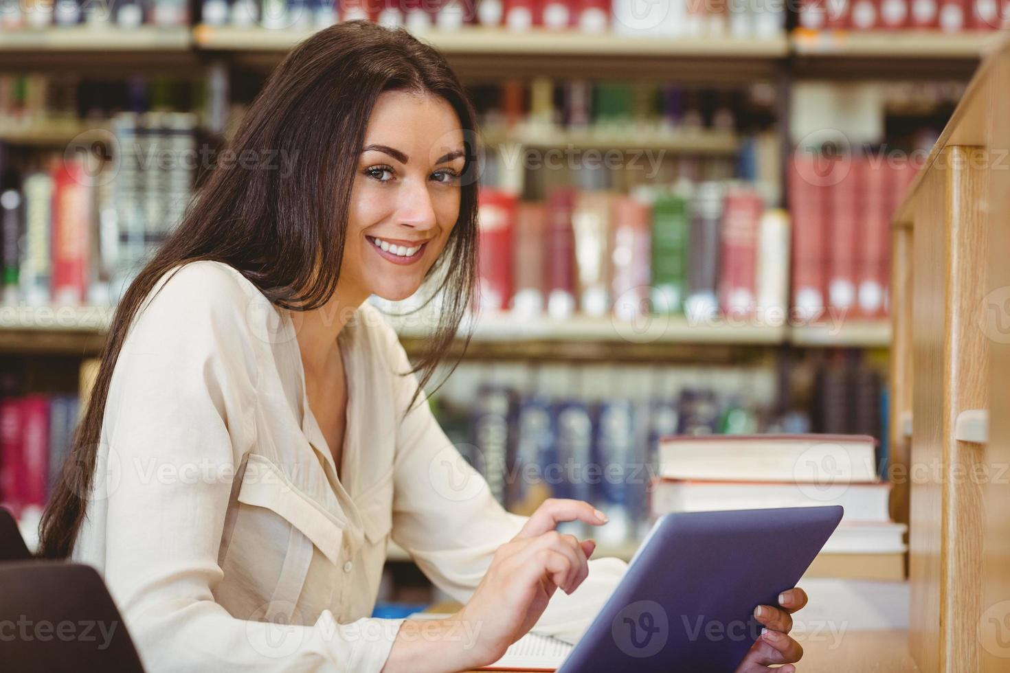 studente grazioso sorridente che per mezzo del computer della compressa foto