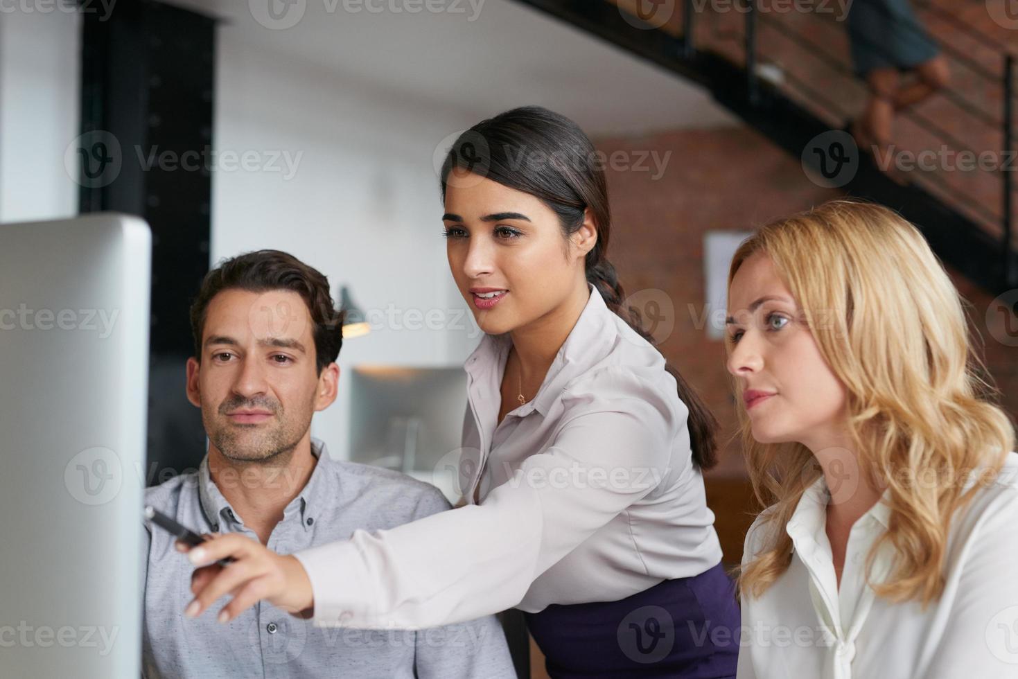donna che punta allo schermo del computer in ufficio occupato foto