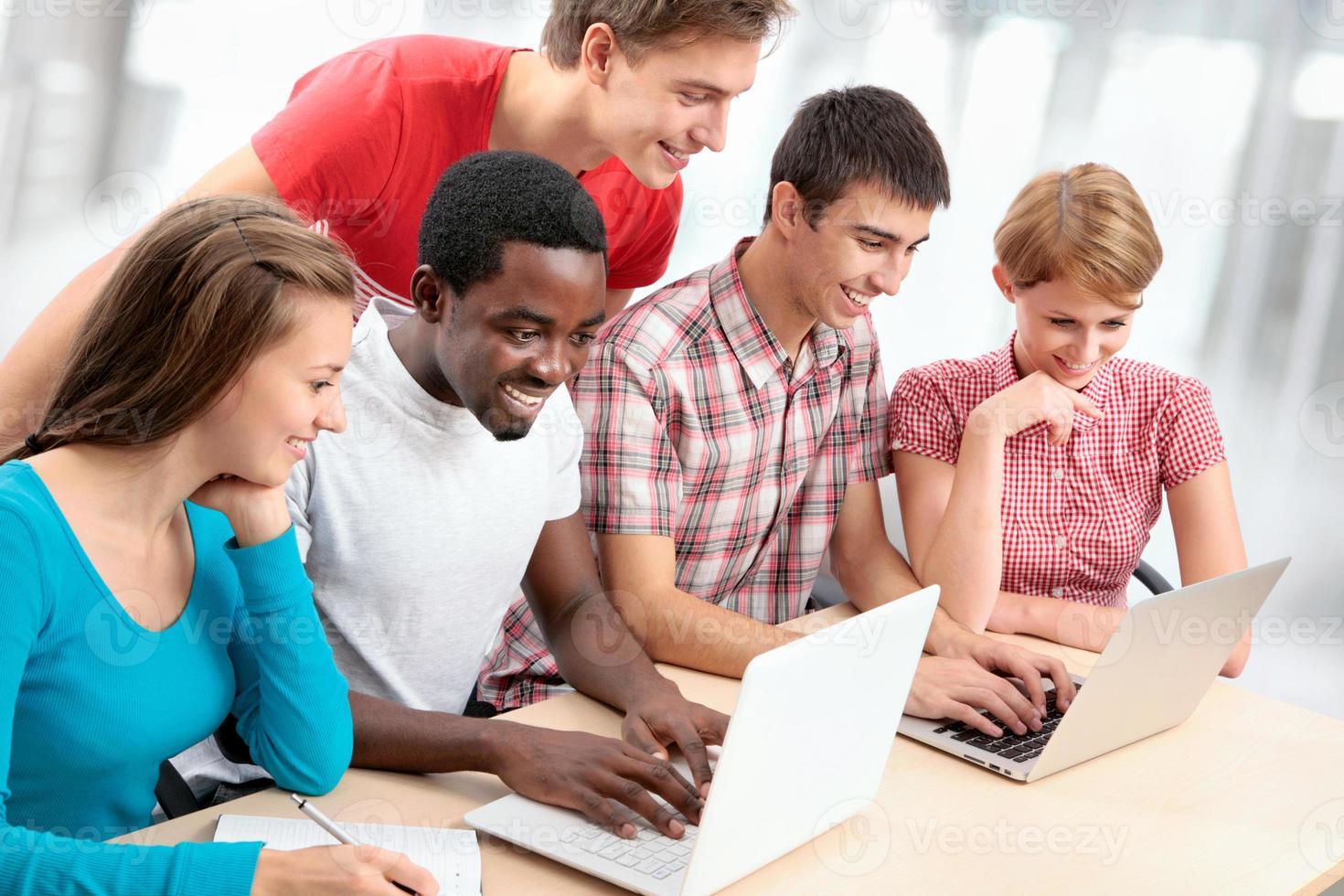 gruppo etnicamente diversificato di studenti che utilizzano computer portatili foto