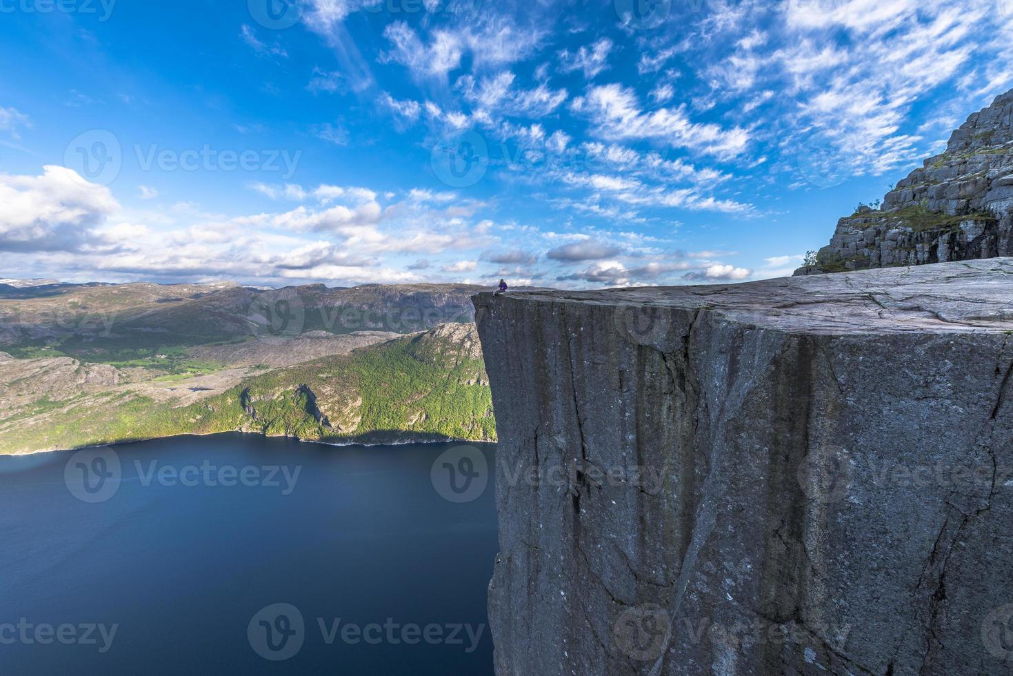 turista che si siede al bordo di roccia famoso del pulpito in Norvegia foto