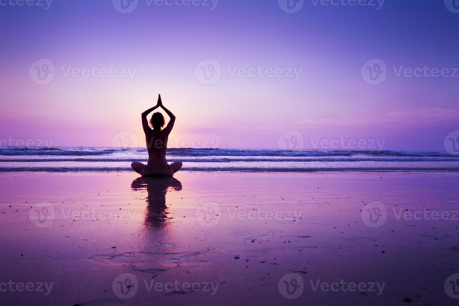donna che pratica yoga sulla spiaggia foto