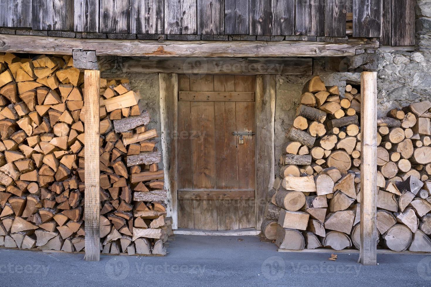 legna da ardere accatastata fuori dalla porta della stalla. foto