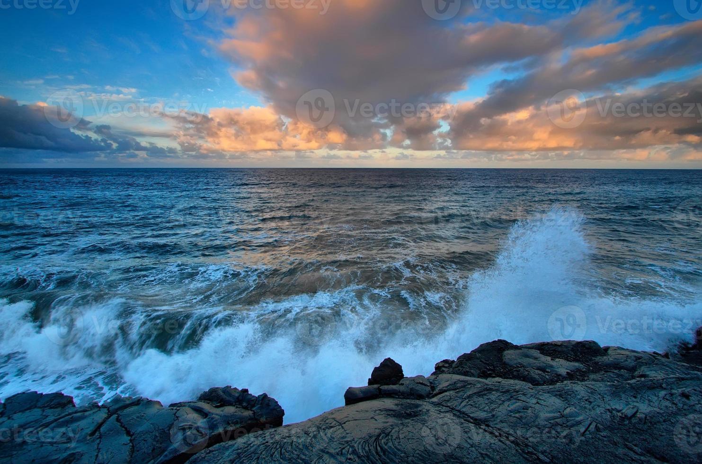 vista sul mare e rocce laviche nere al tramonto foto