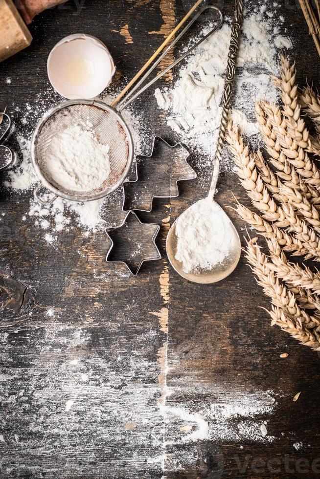 Natale cuocere il fondo in legno con taglierina, farina, cucchiaio e orecchie foto