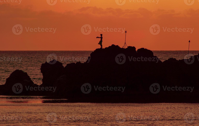 hawaiian cliff diver contro un tramonto arancione foto