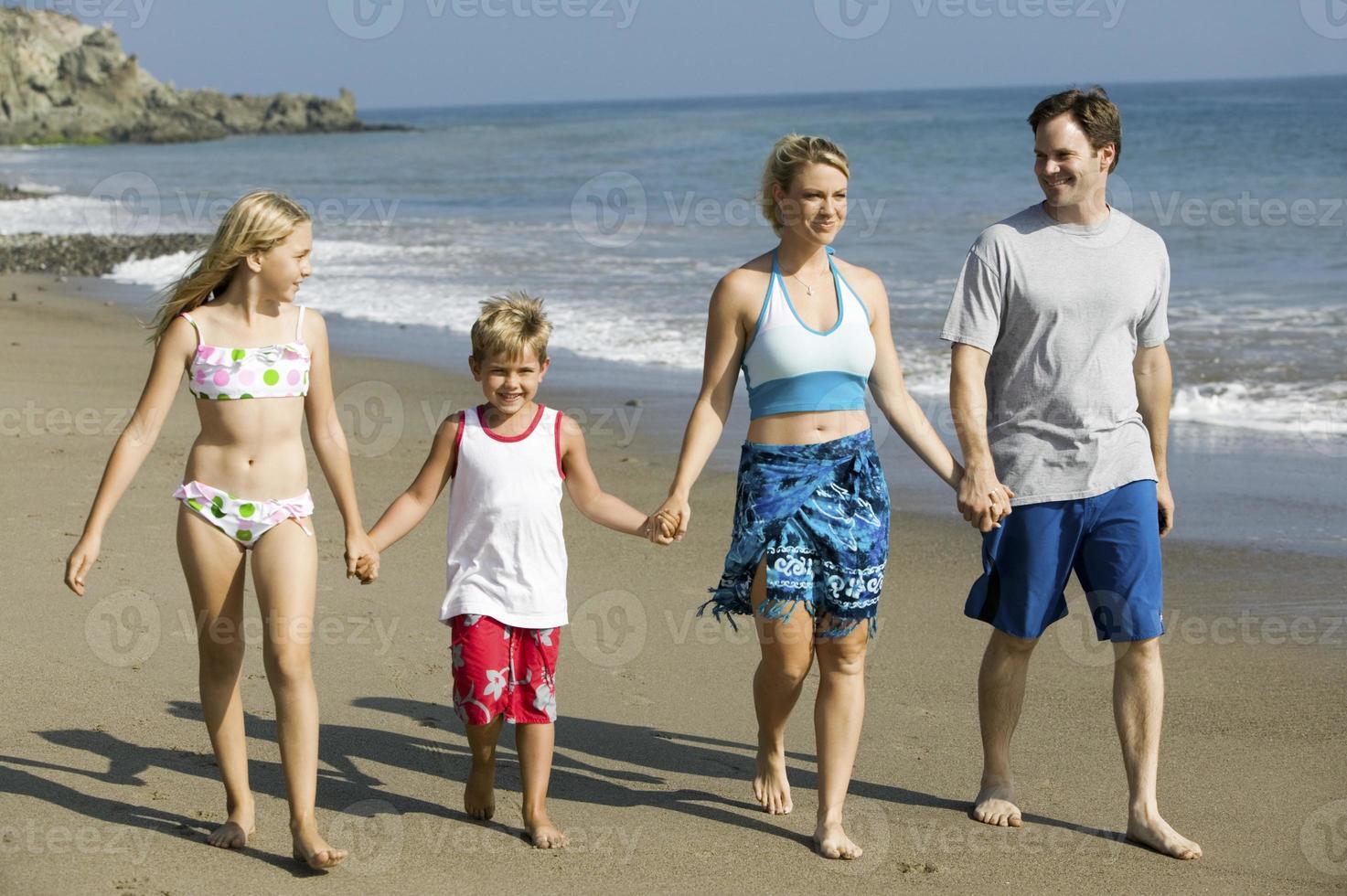 famiglia che si tiene per mano sulla spiaggia foto