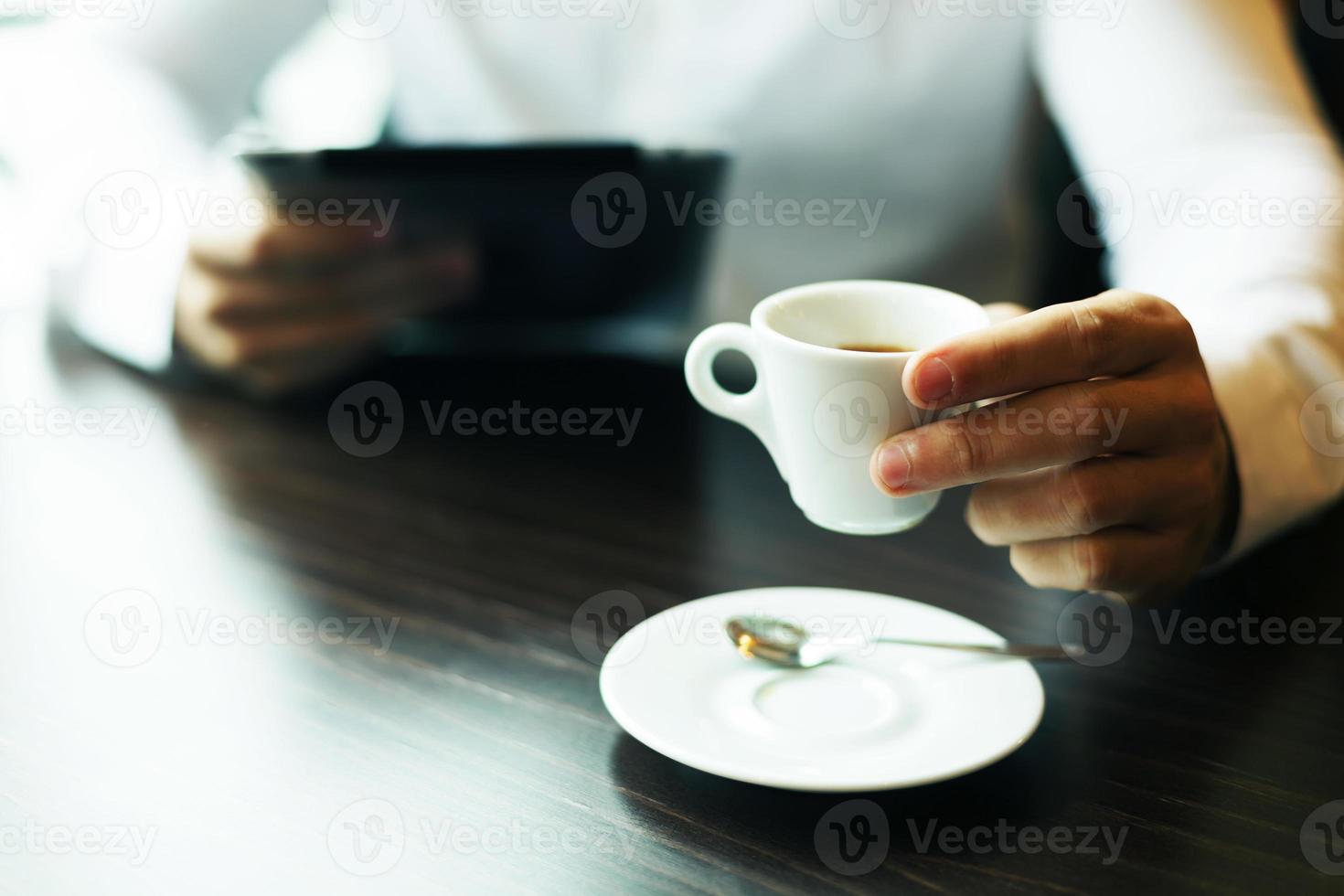 tazza di caffè in mano. computer tablet sfocato foto