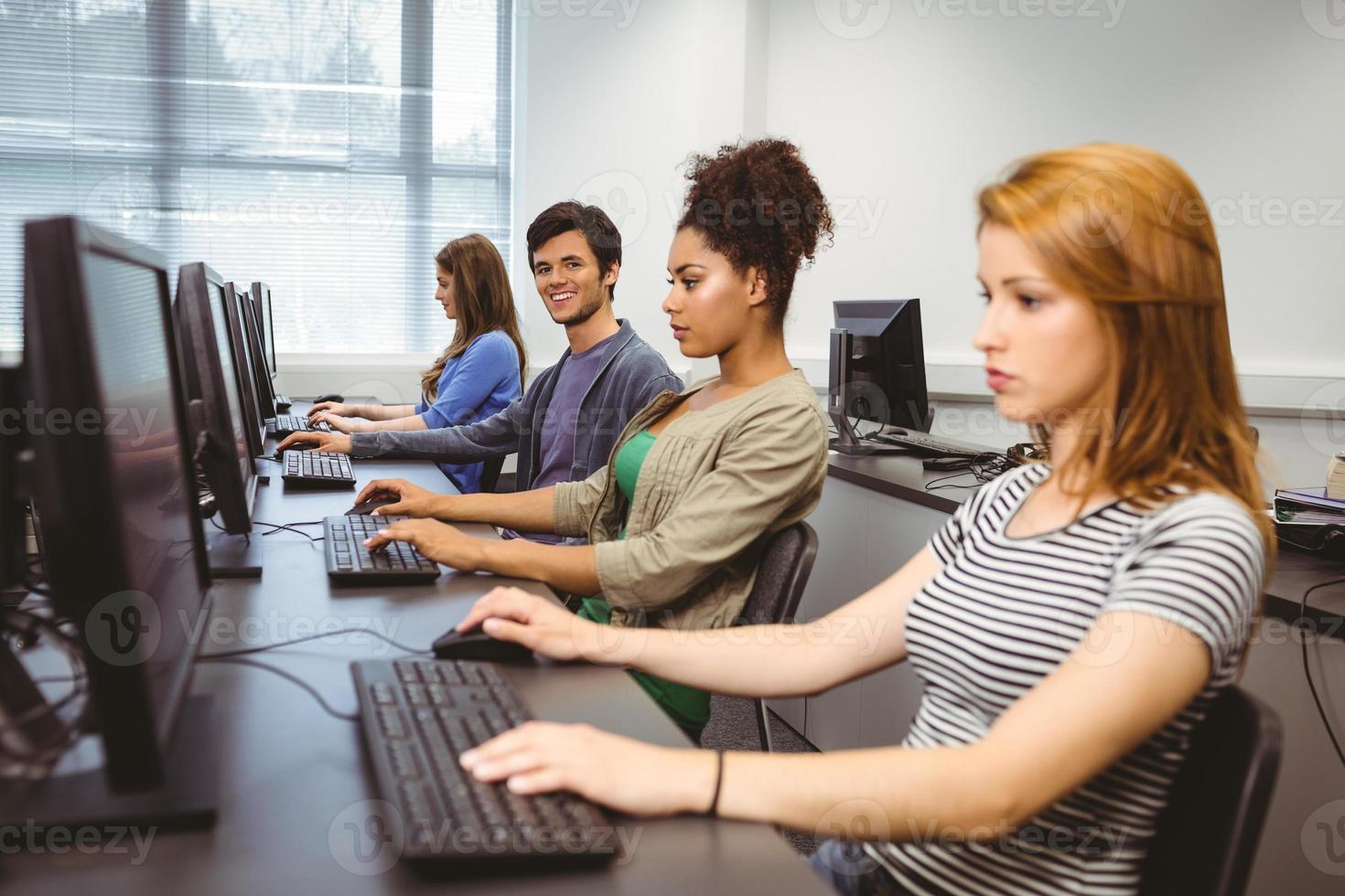 studente felice nella classe del computer che sorride alla macchina fotografica foto