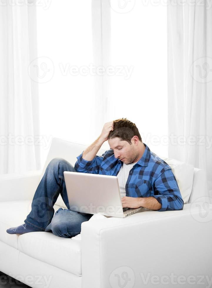 uomo attraente preoccupato con il computer seduto sul divano foto