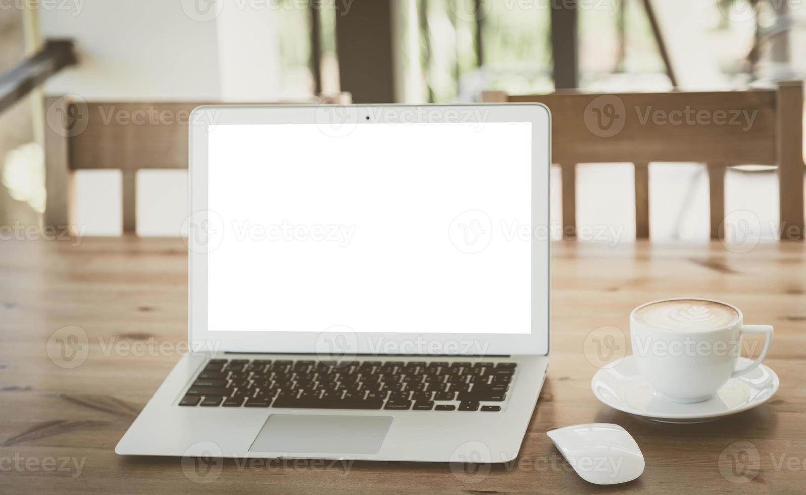 computer portatile con una tazza di caffè sul vecchio tavolo di legno foto