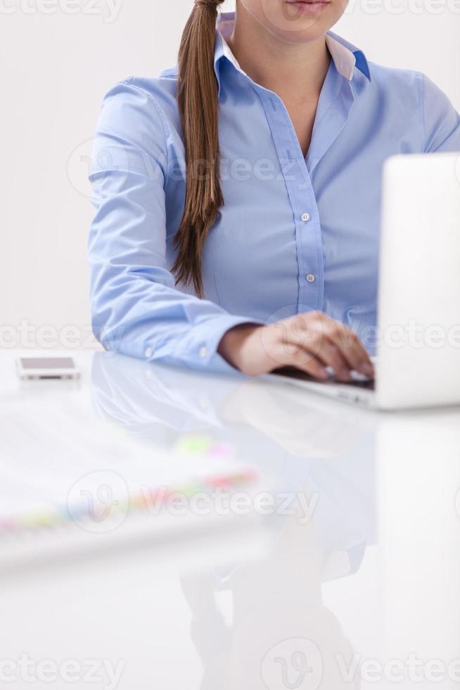 vista del primo piano di bella donna che per mezzo del computer portatile allo scrittorio foto