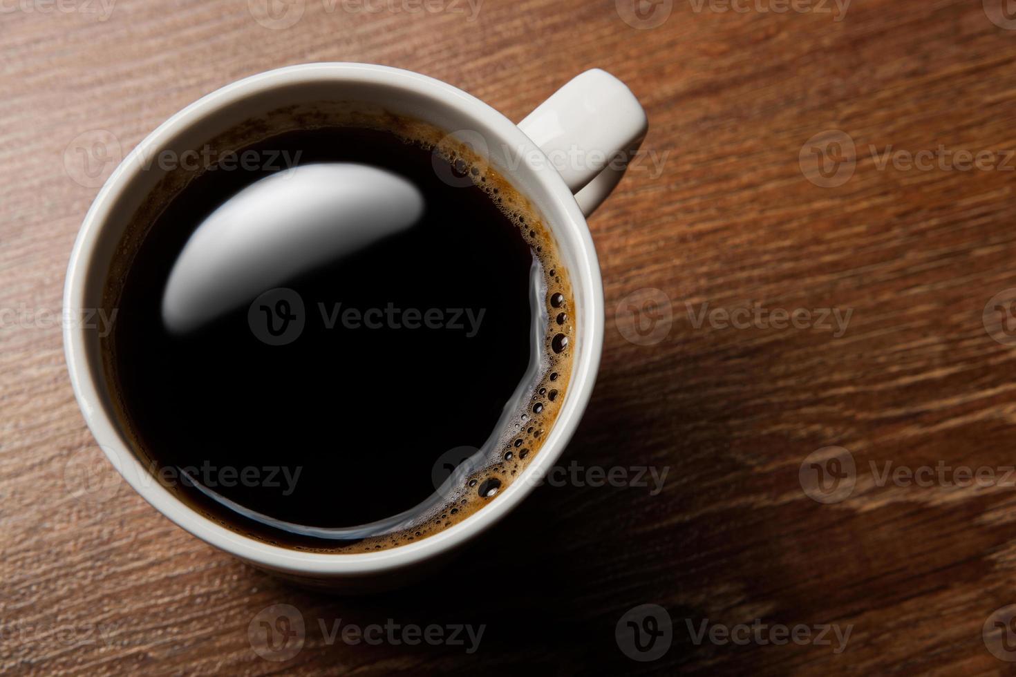 tazza di caffè nero sulla scrivania foto