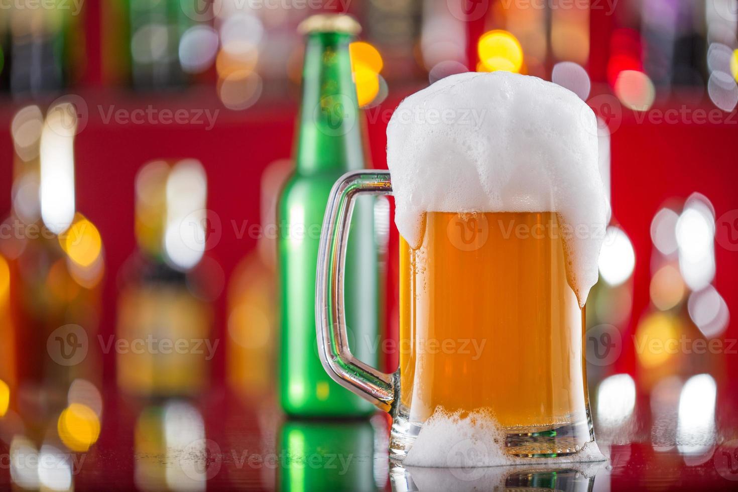 bottiglia di birra con bicchiere sulla scrivania del bar foto