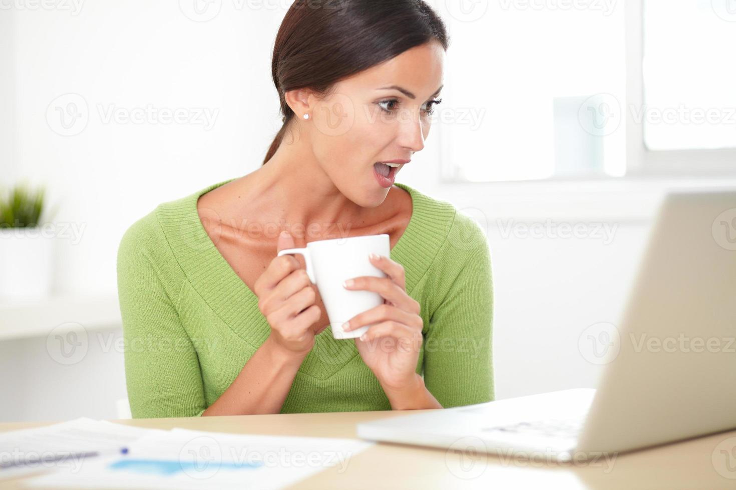 elegante signora scioccata che lavora alla sua scrivania foto