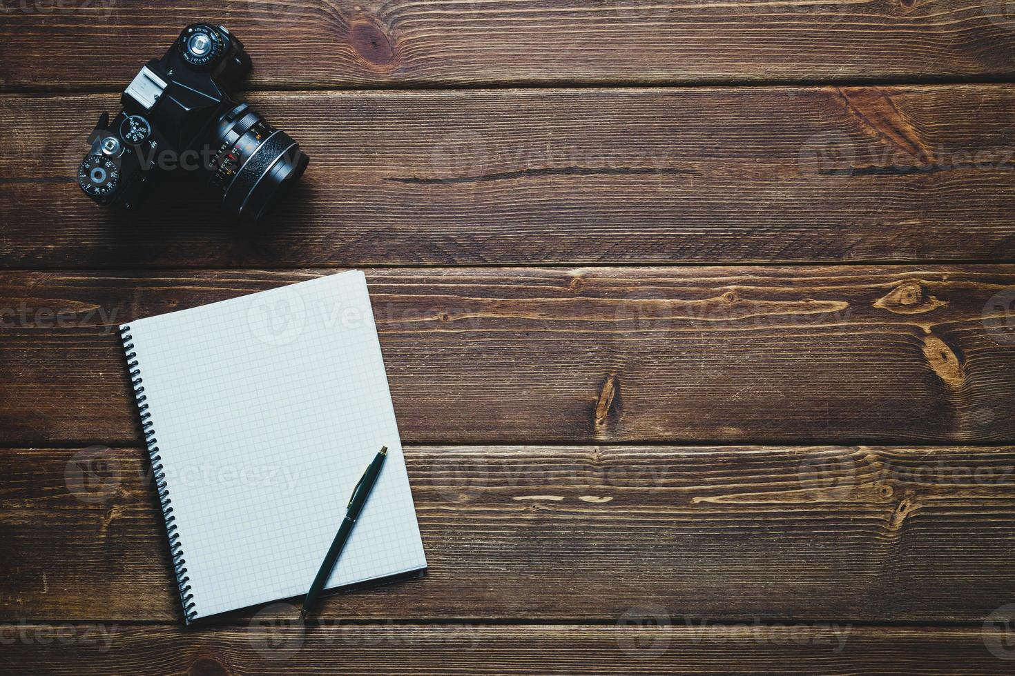 taccuino e macchina fotografica d'epoca sulla scrivania foto