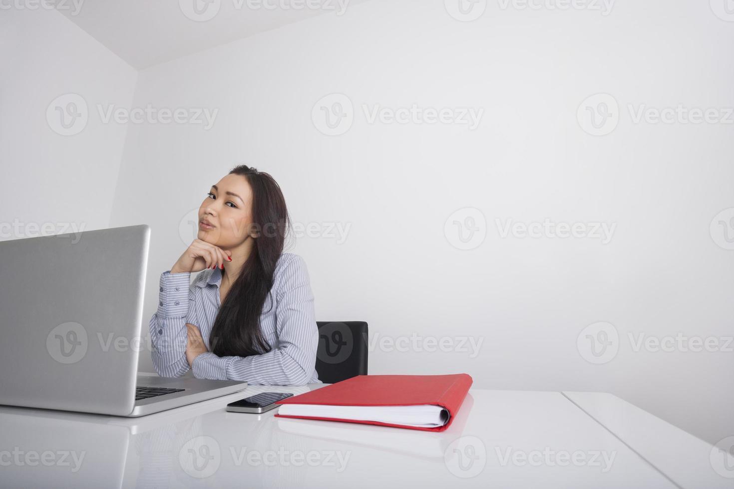 donna di affari premurosa che si siede alla scrivania foto