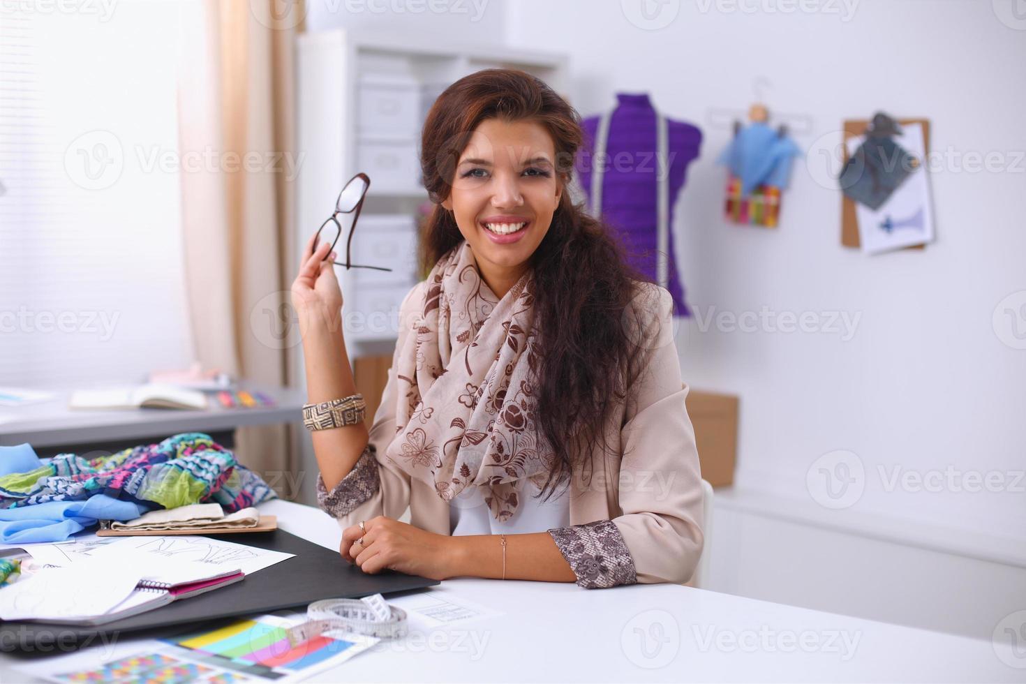 stilista femmina sorridente seduto alla scrivania foto