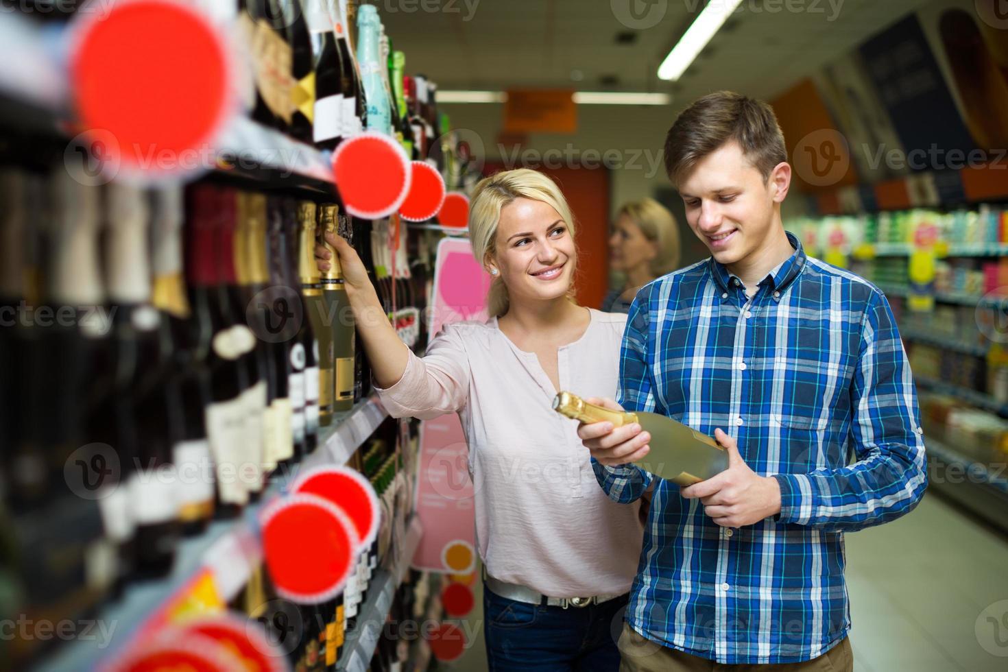 famiglia che sceglie vino al negozio di alimentari foto