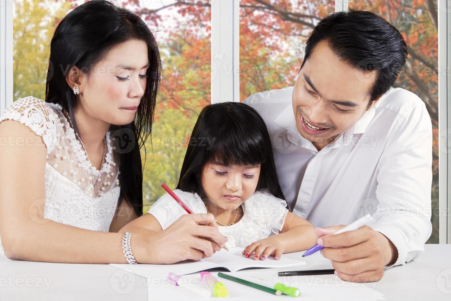 famiglia moderna facendo i compiti sul tavolo foto