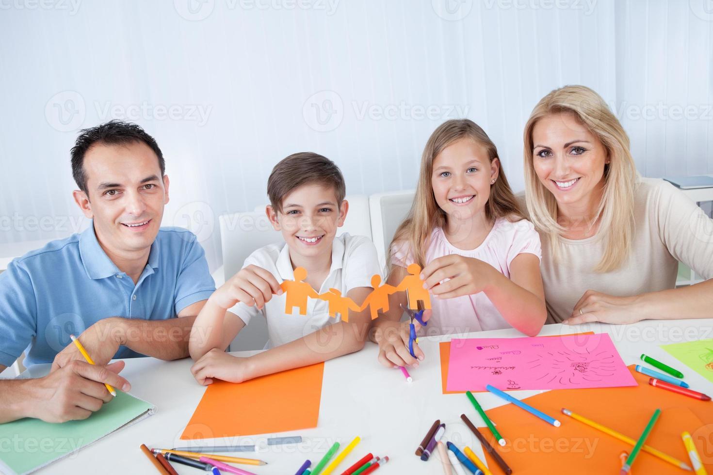 famiglia in possesso di persone di carta in mano foto