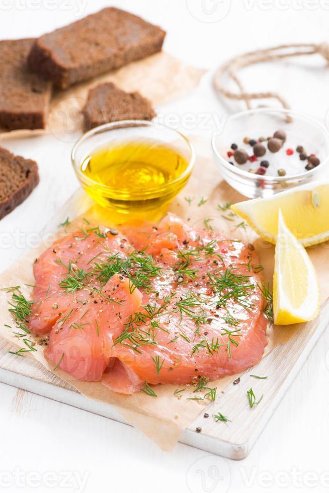aperitivo - salmone salato e pane sul bordo di legno, verticale foto