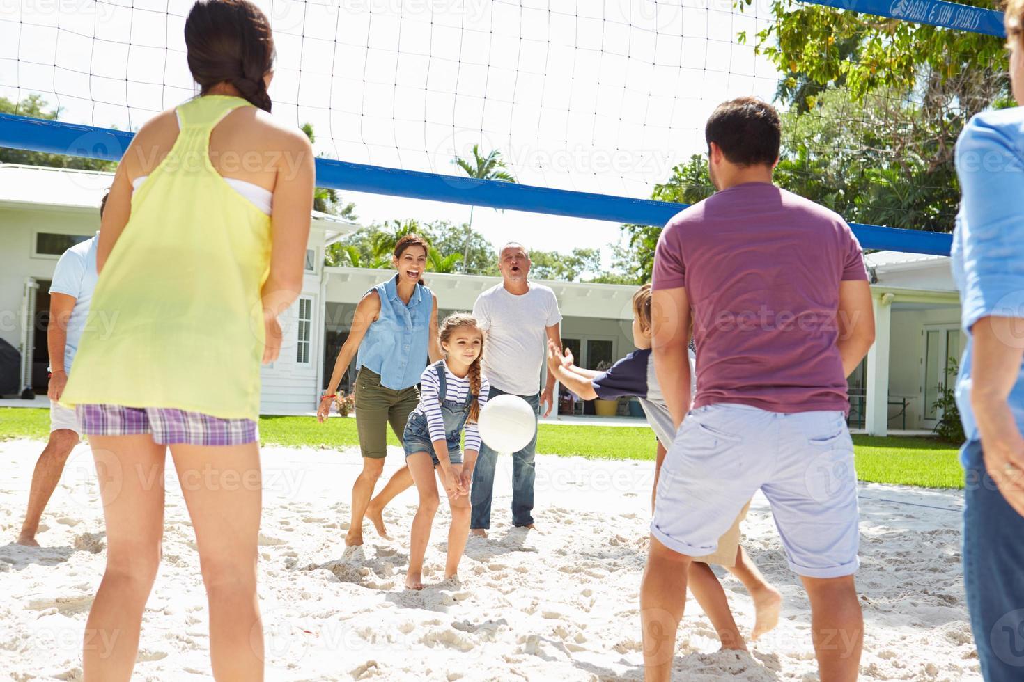 famiglia multi generazione giocando a pallavolo in giardino foto