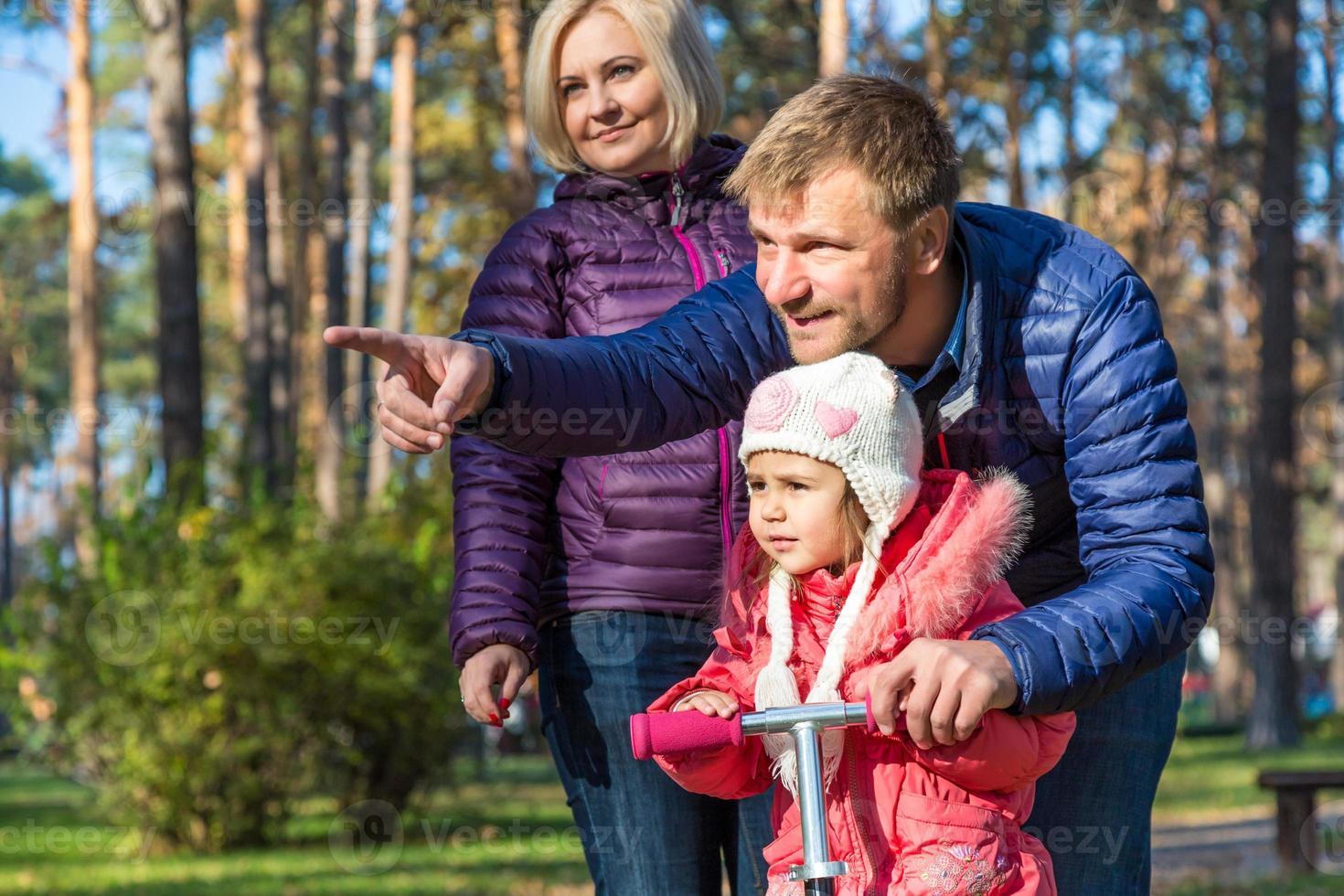 giovane famiglia nell'indicare autunnale della foresta foto