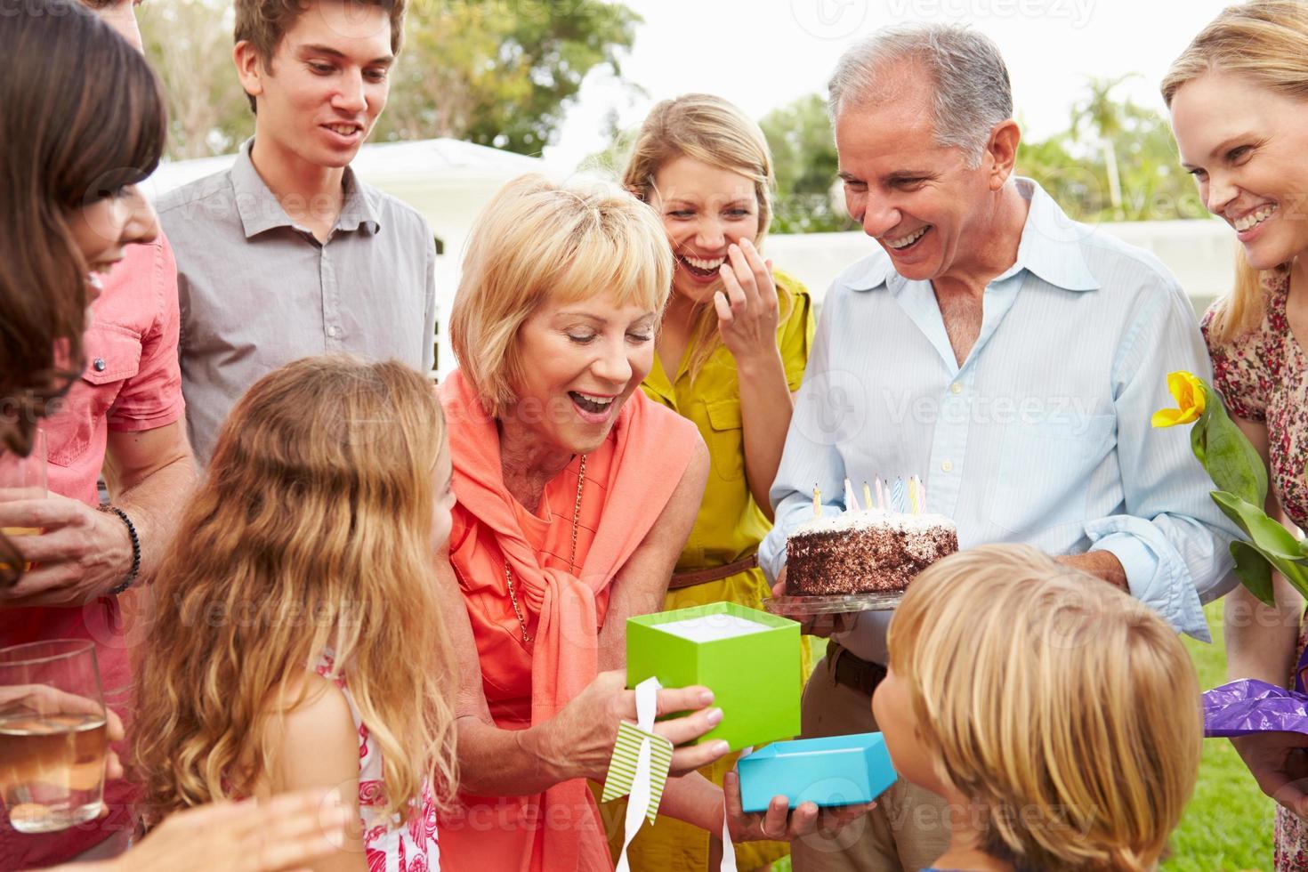 famiglia di diverse generazioni che celebra il compleanno in giardino foto