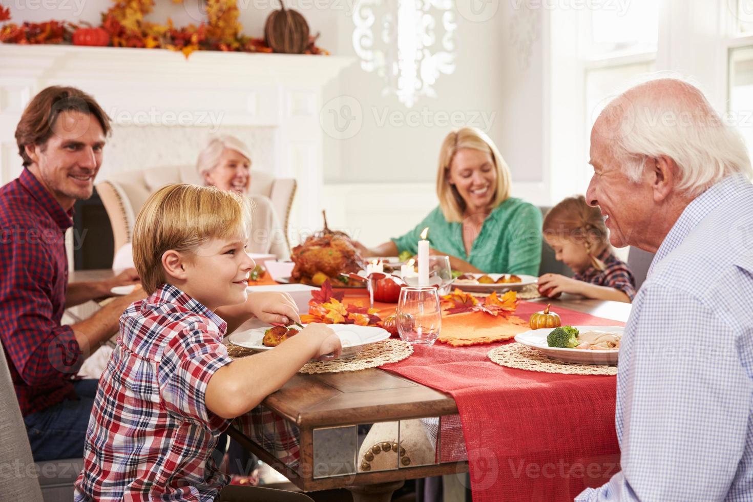 famiglia con i nonni che godono del pasto del ringraziamento al tavolo foto